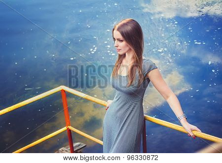 Young woman on the river pier