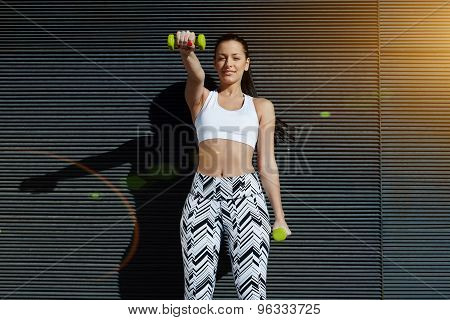 Attractive young woman using dumbbells to work out her arms while training outdoors