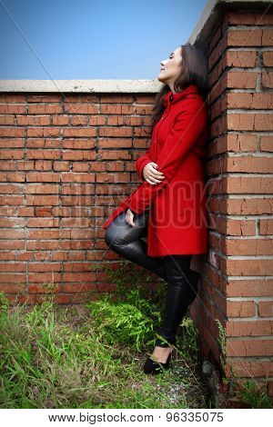 Beautiful Woman In A Red Coat On A Brick Wall In The City