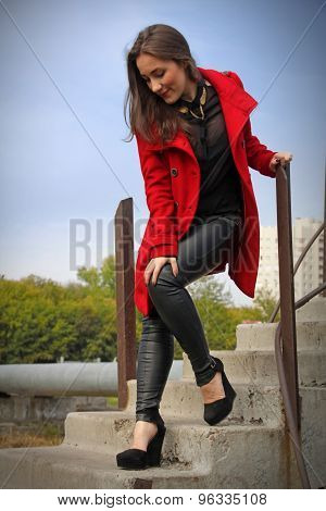 Beautiful Girl In Red Coat Standing On The Stairs In A Graceful Pose