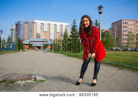 Beautiful Girl In A Red Coat On A Park Alley