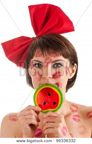 attractive girl with a red bow and lollipop in mouth in lipstick kisses