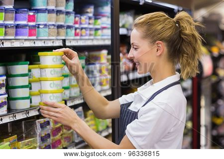 Smiling blonde worker taking a products in shelf in supermarket