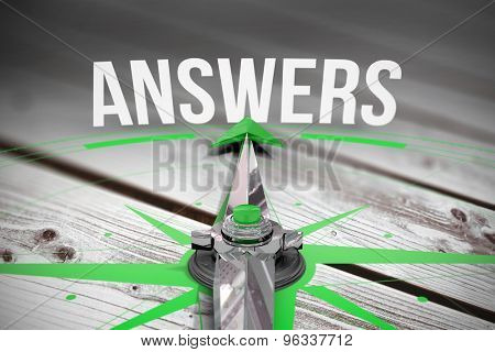The word answers and compass against digitally generated grey wooden planks