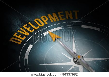 The word development and compass against dark background