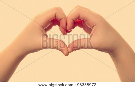 Heart shaped by child hands isolated on white on light background