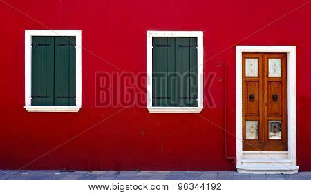 Wooden Door And Two Windows On Red Wall