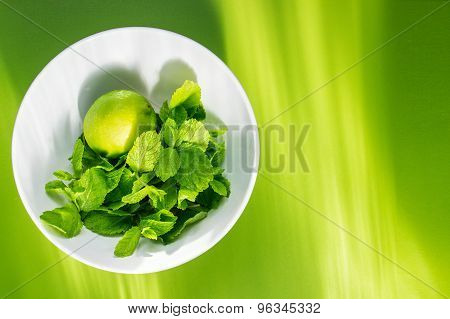 Fresh lime with mint in white cup on green background