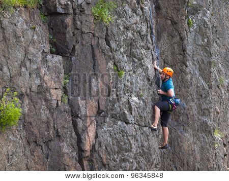 The Climber Climbs In The Helmet On The Wall.