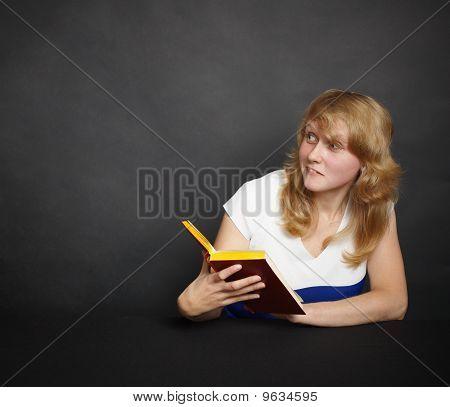 Amusing Girl With Book In Dark