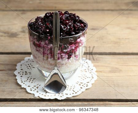 Cottage cheese with black canned currant on wooden background