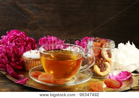 Composition with cup of herbal tea, dried apricots and peony flowers on dark wooden background