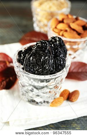Prunes and almonds in glasses with grape leaves on wooden table, closeup