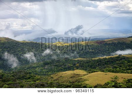 Rain Stripes In The Sky Showering Hills Covered With Woods And Grass