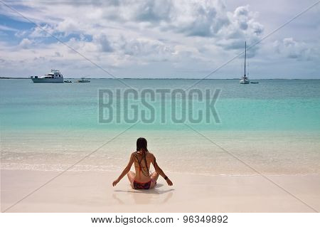 Back View Of Young Woman With Super Long Hair And In Swimsuit Sitting At White Sand Beach