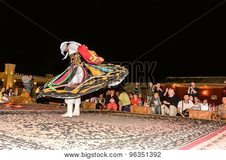 Arab Male Dancer Performing In Front Of A Crowd In Arabian Desert