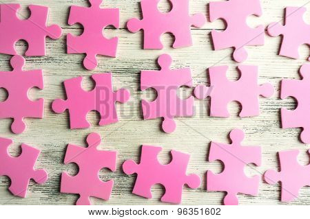 Pink puzzle pieces on wooden table, closeup