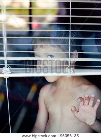 Little cute boy throught window making faces