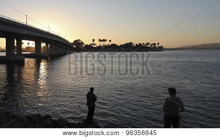 A Pair Of Boys Fish In A Bay At Sunset