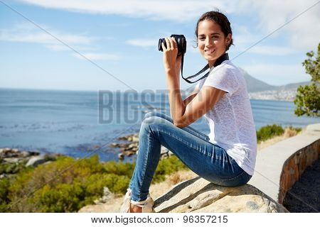young, attractive woman sitting on a rock, poses for a pic near the sea with digital camera in her hand