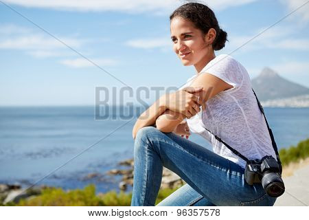 young, attractive female traveler sitting and enjoying the beautiful ocean view with digital camera hung on her shoulder