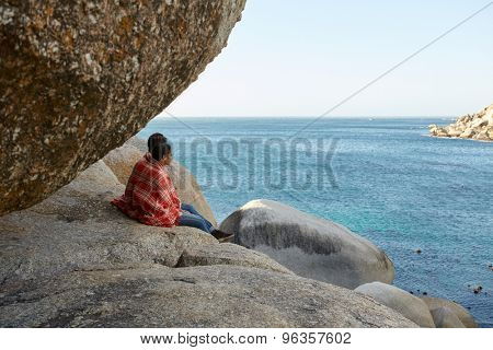 Happy, all cuddled multiracial couple, sitting on the rocks, overlooking the ocean and enjoying the view
