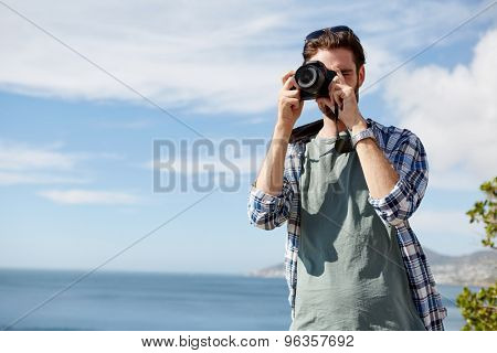 young, attractive man standing and taking pics of the ocean using a digital camera