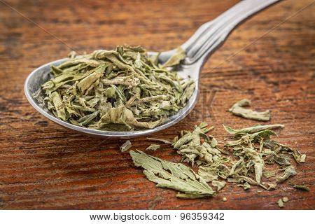 stevia dried leaves on a tablespoon against rustic woof - natural sweetener, sugar substitute