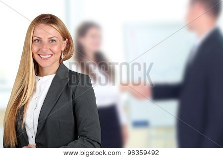 The Beautiful Smiling Business Woman  Portrait. Handshake Between Two Collegues Behind