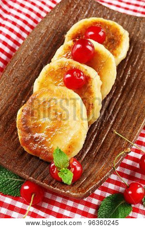 Fritters of cottage cheese with berries in plate, closeup