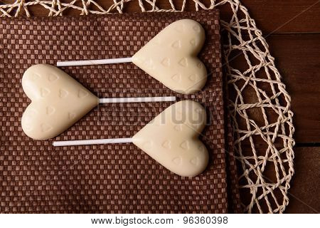 Chocolate heart shaped candies on sticks on brown napkin, closeup