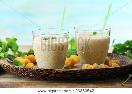 Glasses of raspberry smoothie on wooden table on turquoise background