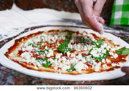 Preparing pizza on marble table, closeup