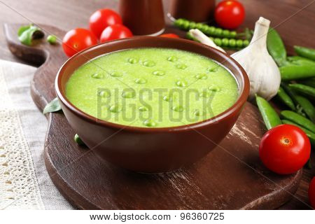 Tasty peas soup and vegetables on table close up