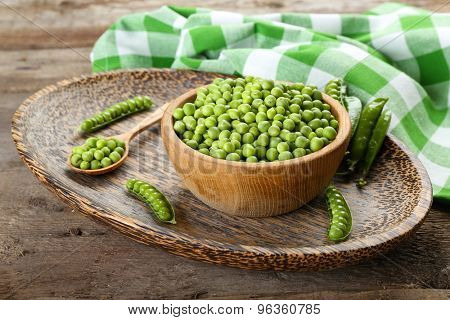 Fresh green peas in bowl on wooden table, closeup