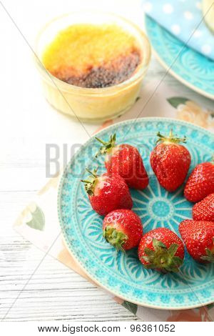 Creme brulee dessert with fresh strawberry berries on napkin, on color wooden background