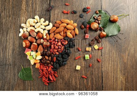 Nuts and dried fruits arranged in heart shape on wooden background