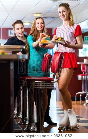 Friends or couple eating fast food in American fast food diner, the waitress wearing a short costume and roller skates