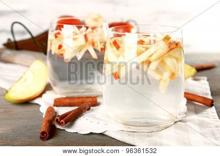 Glasses of apple cider with fruits and cinnamon on table close up
