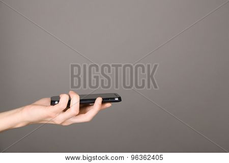 Female hand using mobile phone on gray background