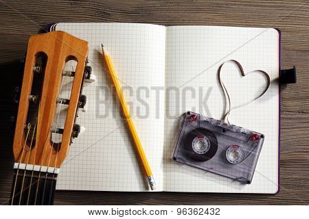 Music recording scene with classical guitar, memo pad and cassette on wooden table, closeup