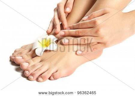 Female feet at spa pedicure procedure with plumeria isolated on white