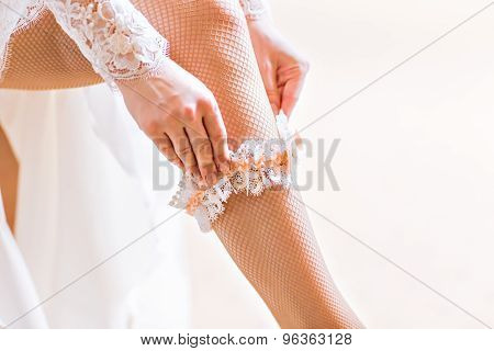 bride dresses garter on the leg.