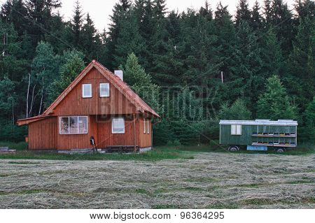 Wood Log Cabin Near Forest In Cloudy Day And Mobile Transport Car For Beehive Honey