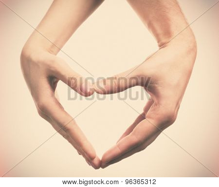 Heart shaped by male and female hands on light background