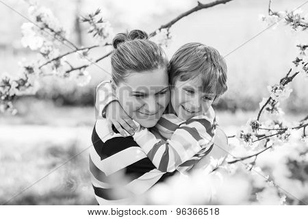 Young Mother And Little Kid Boy Having Fun In Blooming Garden