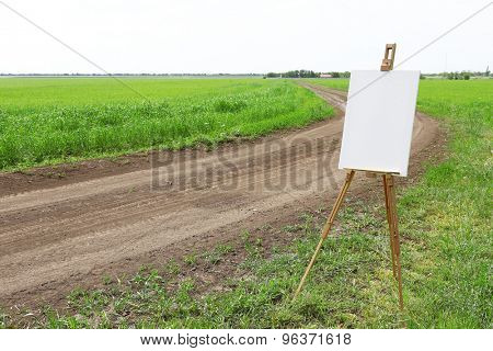 Easel with canvas near country road