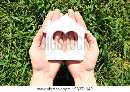 Female hands holding house over green grass background