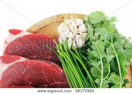 butchery : fresh raw beef lamb fillet ready to cooking with green stuff on wooden plate isolated over white background