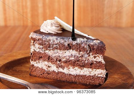 sweet brownie chocolate cream cake topped with white chocolate and cream with chocolate with chocolate sauce on wooden background
